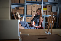 Businesswoman in office warehouse having coffee Stock Image