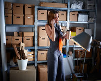 Businesswoman in office warehouse with mobile Stock Photos