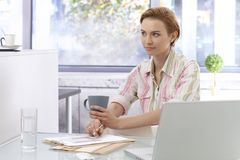 Businesswoman in office. Young businesswoman sitting at desk in office, working, drinking tea Royalty Free Stock Photo