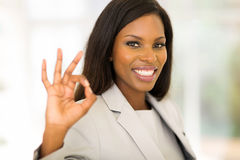 Businesswoman ok hand sign. Cheerful african american businesswoman giving ok hand sign royalty free stock photography