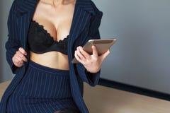 Businesswoman online flirt. Secretary in black bra online flirt on tablet, desire stock images