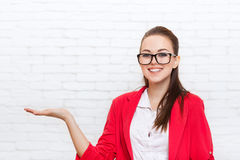 Businesswoman open palm hand gesture to copy space wear red jacket glasses smile Royalty Free Stock Photography