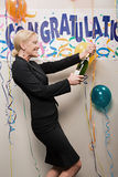 Businesswoman opening bottle of champagne Stock Photos