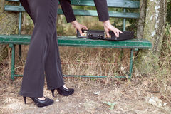 Businesswoman opens briefcase on a bench Royalty Free Stock Image