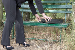 Businesswoman opens briefcase on a bench Stock Photography