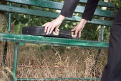 Businesswoman opens briefcase on a bench Stock Photos