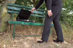 Businesswoman opens briefcase on a bench Royalty Free Stock Photography