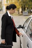 Businesswoman opens a car door Royalty Free Stock Photography