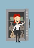 Businesswoman opens a safe with money. Happy smiling businesswoman opening the door of safe with money bags and stacks, for safety or security concept design Stock Photos
