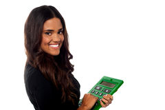 Businesswoman operating big green calculator. Smiling young woman posing with calculator over white stock illustration