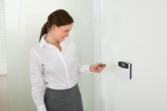 Businesswoman Operating Door Security System Royalty Free Stock Photos