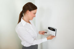 Businesswoman Operating Door Security System Stock Photo