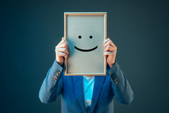 Businesswoman is optimistic, holding smiley emoticon over face Royalty Free Stock Image