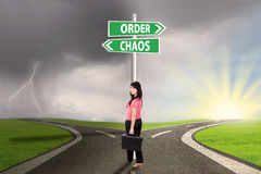 Businesswoman with order and chaos direction. Businesswoman standing on the road with signpost of order and chaos Royalty Free Stock Images