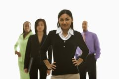 Businesswoman with others. Portrait of Indian businesswoman smiling with hands on hips with others in background Stock Images