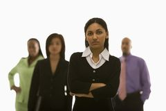 Businesswoman with others. Portrait of Indian businesswoman  with arms crossed with others in background Stock Photo