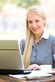Businesswoman at outdoor cafe. Young woman sitting outdoors with laptop on table, portrait Stock Image