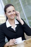 Businesswoman at outdoor cafe. Businesswoman Sitting Outside and talking on cell phone Royalty Free Stock Photo
