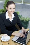Businesswoman at outdoor cafe. Businesswoman with laptop drinking coffee Royalty Free Stock Photo