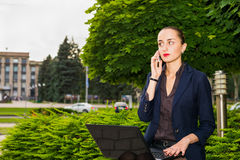 Businesswoman outdoor. Businesswoman talking on the phone and working on her laptop outdoor Stock Photos