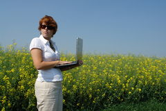 Businesswoman outside. Businesswoman working outside with wireless connectivity in the middle of a yellow flower field Stock Images