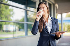 Businesswoman outside with coffee and tablet Stock Photos