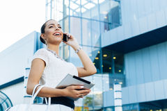 Businesswoman outside on phone with digital tablet in hand Royalty Free Stock Photos