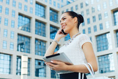 Businesswoman outside on phone with digital tablet in hand Royalty Free Stock Image