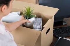 Businesswoman Packing Belongings In Cardboard Box. Young Businesswoman Packing Belongings In Cardboard Box At Desk Stock Photo
