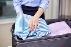 Businesswoman packing clothes into travel bag Stock Photo