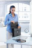 Businesswoman packing out briefcase in office Royalty Free Stock Images