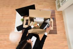 Businesswoman packing personal belonging in box Royalty Free Stock Photography