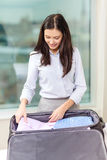 Businesswoman packing things in suitcase Stock Images