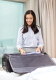 Businesswoman packing things in suitcase Stock Photography