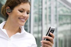 Businesswoman with palmtop. Young woman using palmtop outdoors Royalty Free Stock Photography