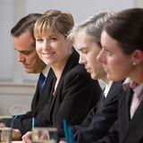 Businesswoman on panel of co-workers Stock Images
