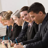 Businesswoman on panel of co-workers Royalty Free Stock Photography