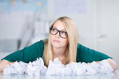 Businesswoman With Paper Balls On Desk Looking Away Royalty Free Stock Photo