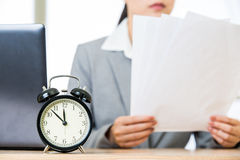 Businesswoman with papers over table with alarm clock laptop Royalty Free Stock Photos