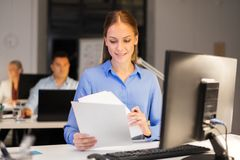Businesswoman with papers working at night office stock photography
