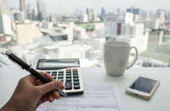 Businesswoman with paperwork and calculator on desk Royalty Free Stock Photo