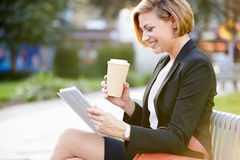 Businesswoman On Park Bench With Coffee Using Digital Tablet Stock Images