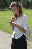 Businesswoman in the park sending a text message Stock Image