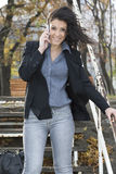 Businesswoman in a park talking mobile phone. Royalty Free Stock Photos