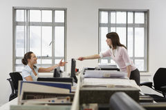 Businesswoman Passing Document To Colleague Over Desk In Office. Side view of young businesswoman passing document to colleague over desk in office Stock Images
