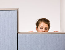 Businesswoman peering over cubicle wall Royalty Free Stock Photo