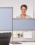 Businesswoman peering over cubicle wall Royalty Free Stock Images
