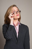 Businesswoman peering over glasses Royalty Free Stock Image