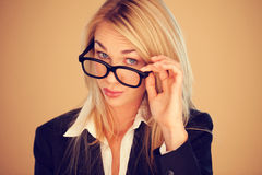 Businesswoman peering over her glasses Stock Image