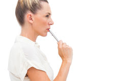 Businesswoman with pen on mouth Stock Image